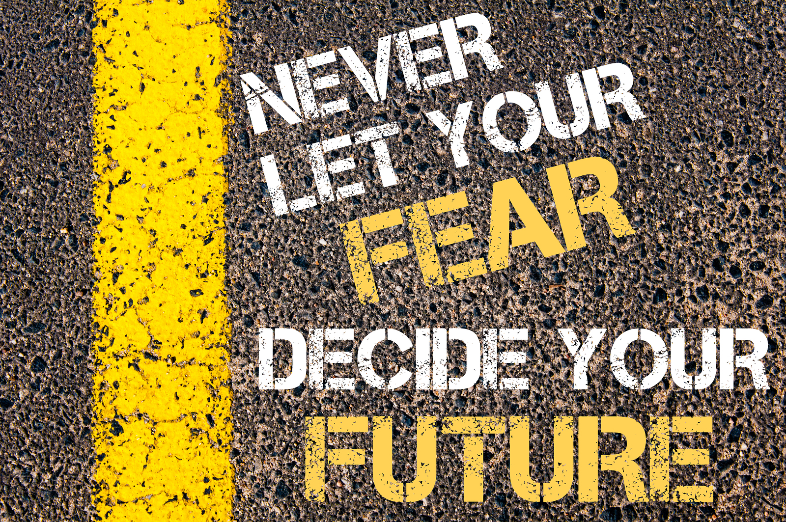 NEVER LET YOUR FEAR DECIDE YOUR FUTURE motivational quote. Yellow paint line on the road against asphalt background. Concept image